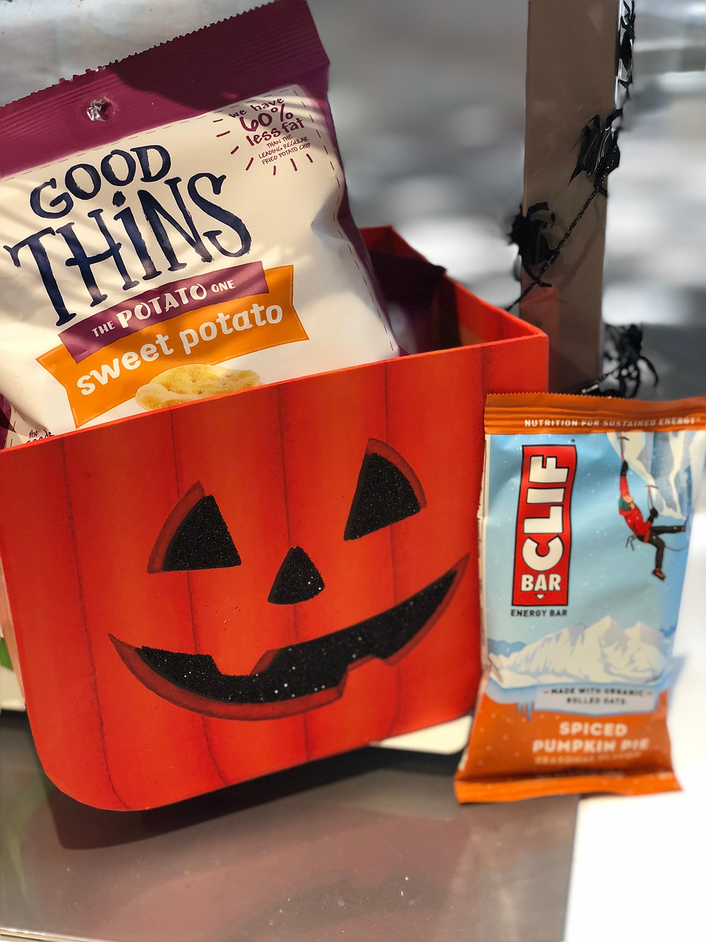 A cliff bar and sweet potato chips by a pumpkin box.