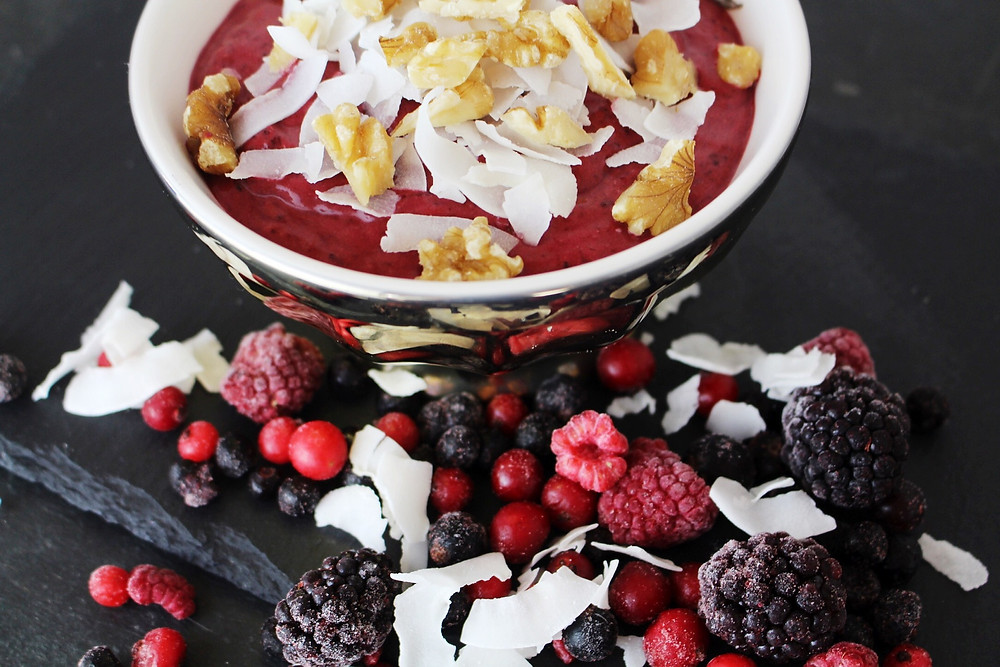 A smoothie bowl topped with walnuts and coconut flakes next to berries and coconut flakes displayed on the table.