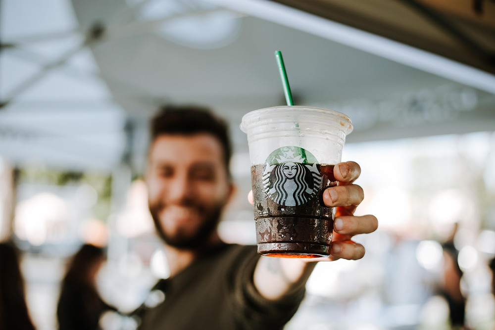 Camera focused on an iced coffee that a guy is holding.