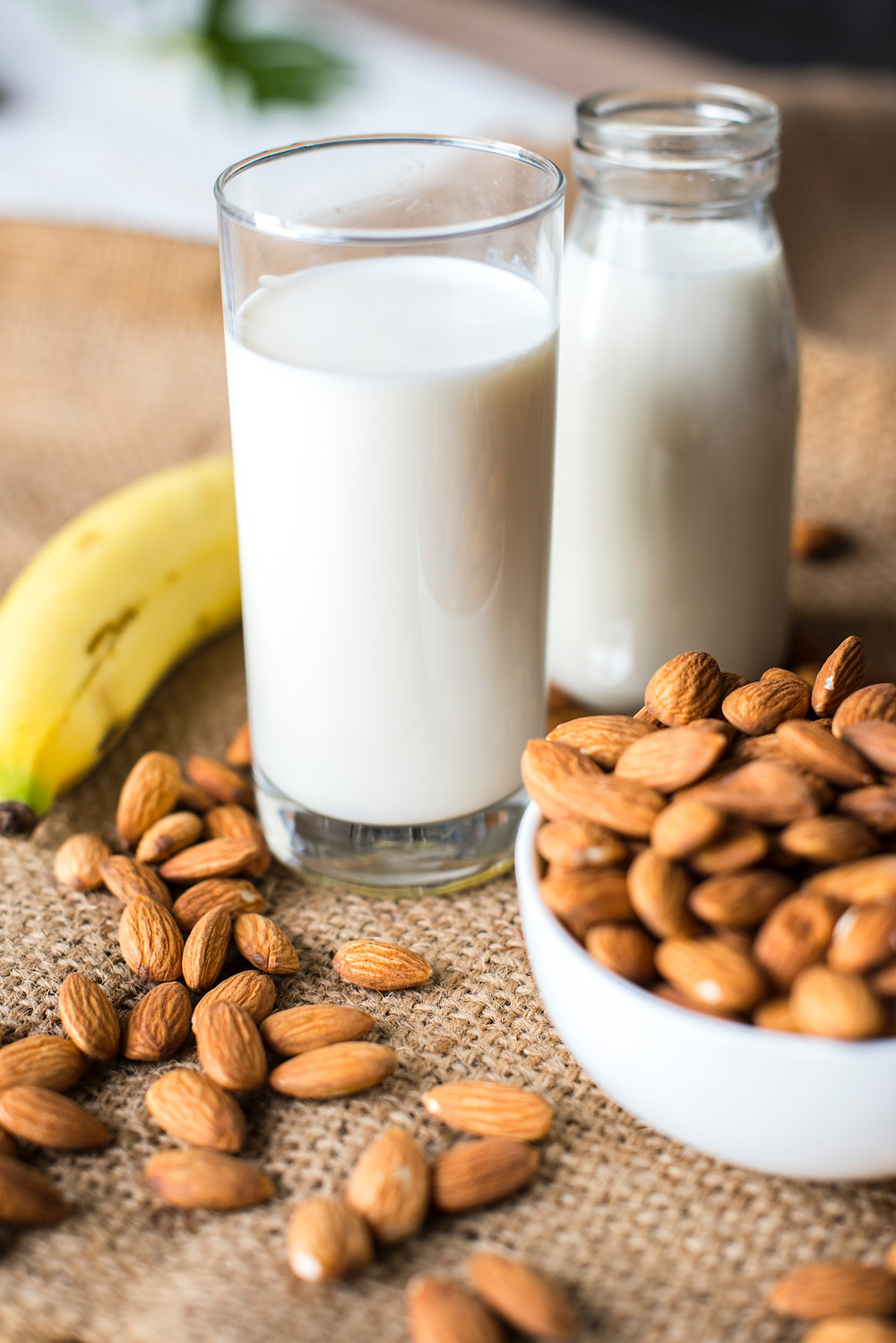 Two glasses of milk with almonds and a banana.