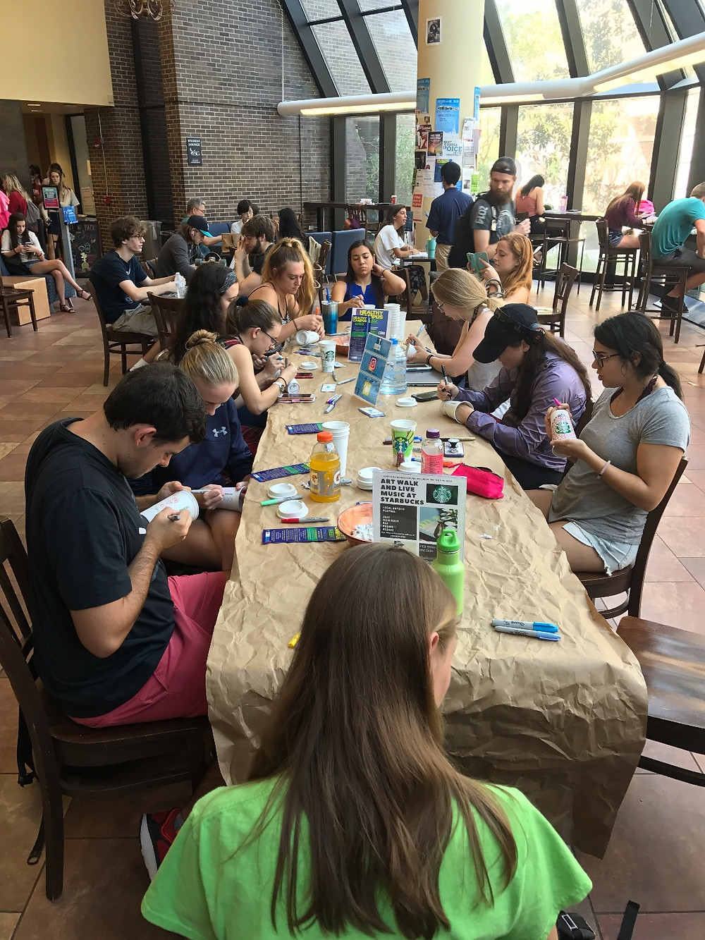 A long table at Starbucks with many people painting mugs.