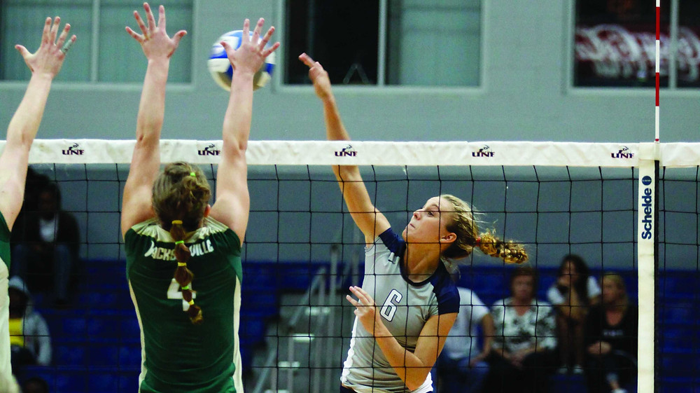A girl spiking the all over the net with two blockers in Volleyball
