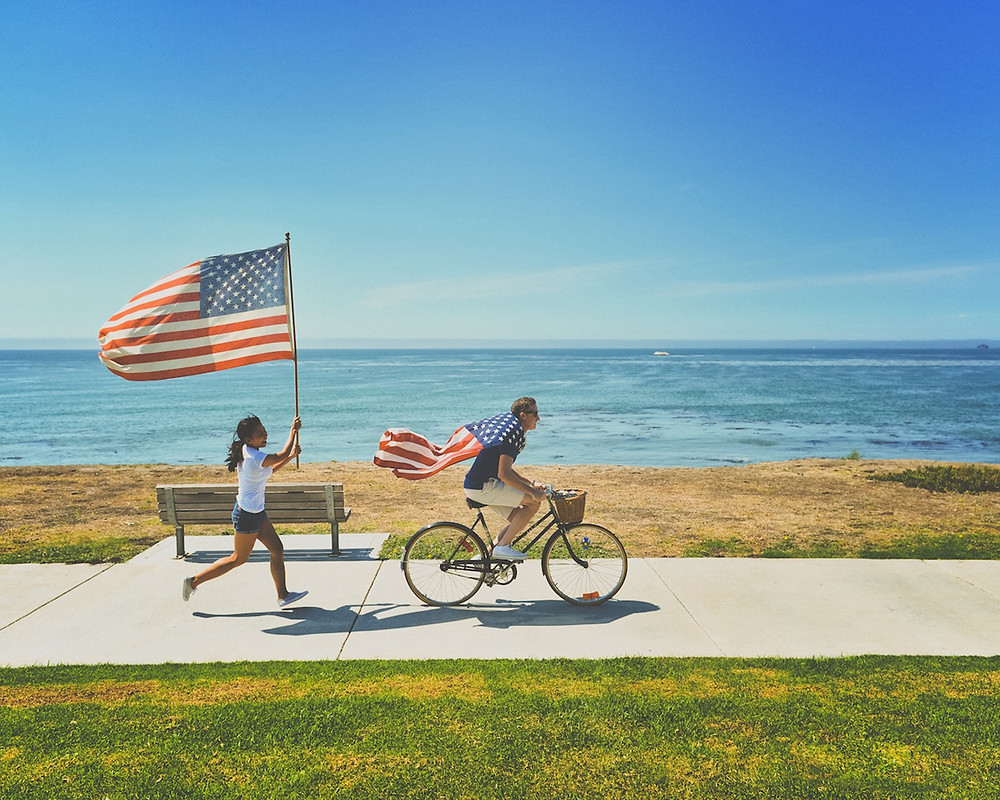 A guy on a bike with the American flag as his cape and a girl running behind him with an American Flag