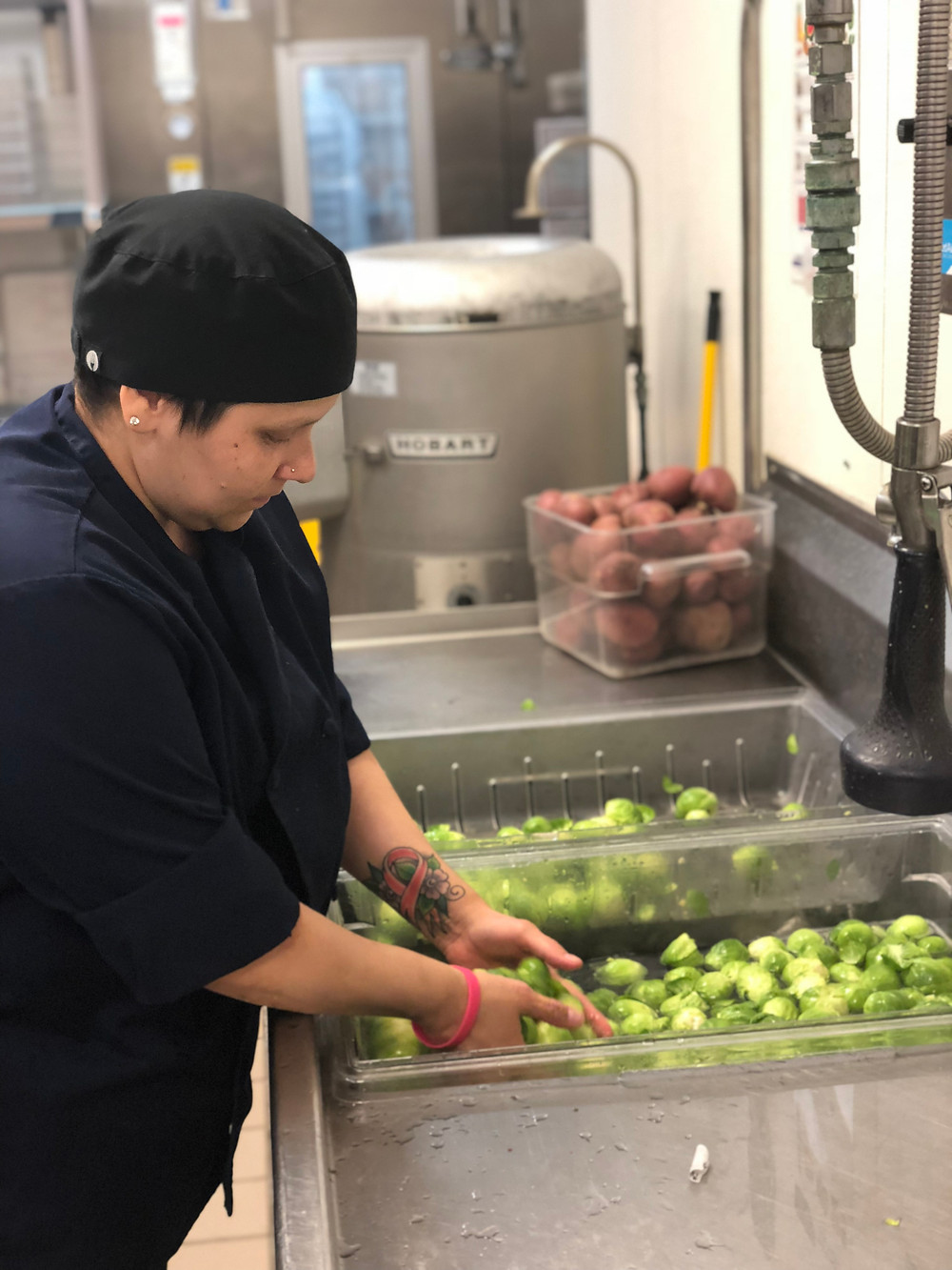 A cafe worker washing Brussel sprouts