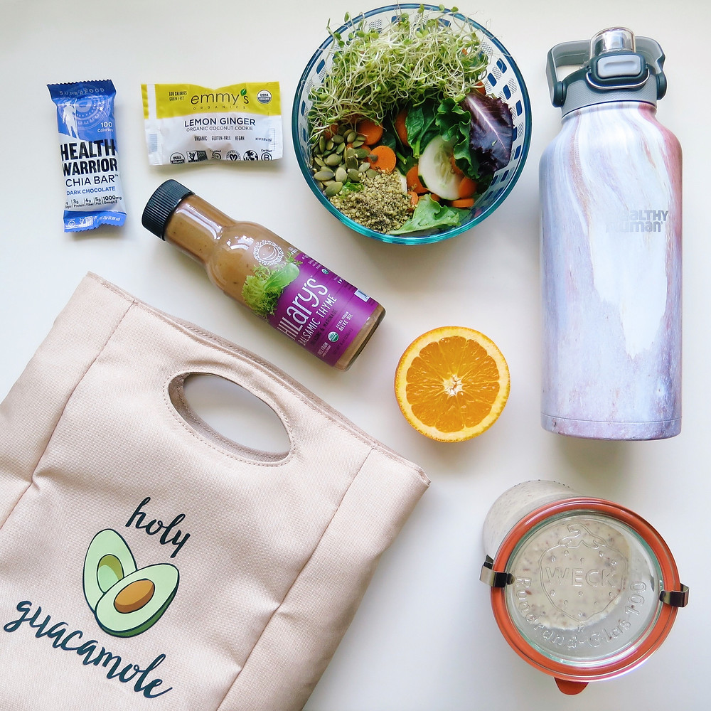 Birds eye view of a salad, dressing, orange, and a chia bar along with a lunch box laid on a table.