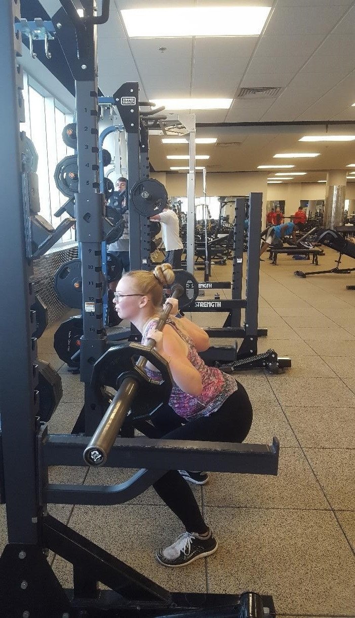 A girl doing a squat under a barbell.