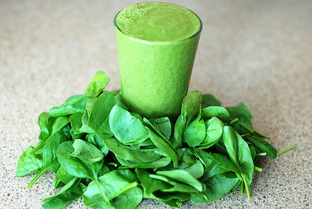 A green smoothie with a handful of spinach around the smoothie.