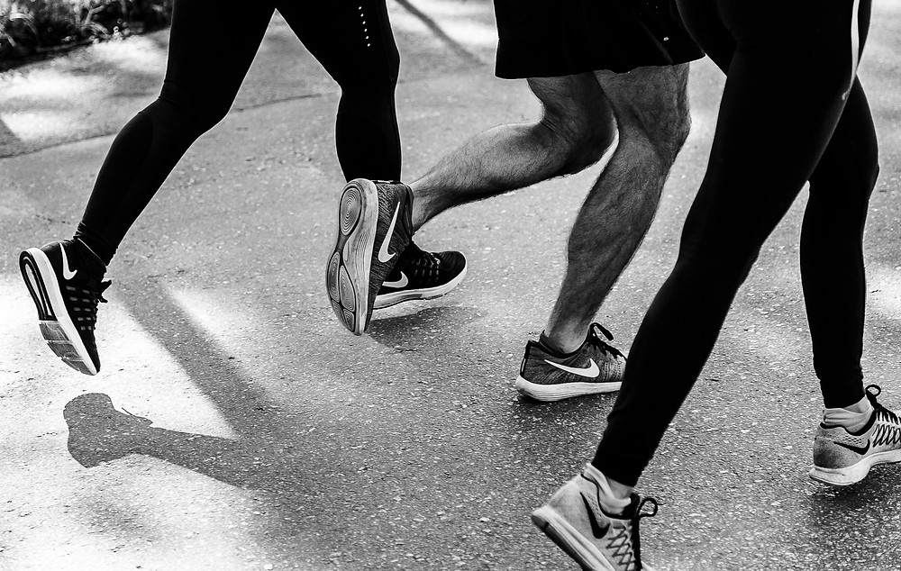 Lower half of three people's legs running.