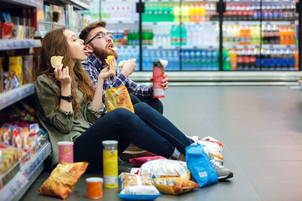 A male and female sitting in a grocery store aisle eating and drinking snacks.
