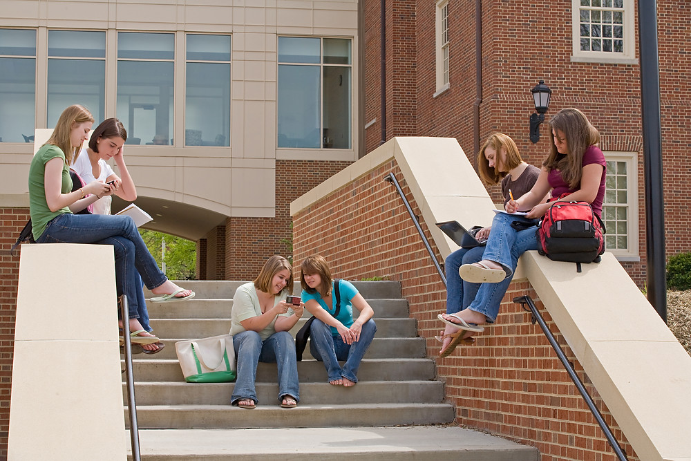 Six females sitting on steps with books, phones, and laptops studying.
