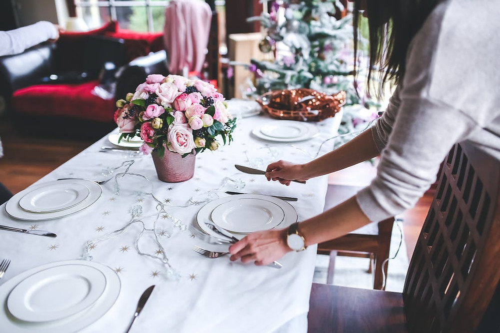 Someone setting a table with flowers and a white tablecloth.
