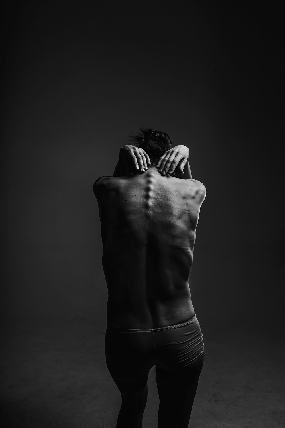 The back of a thin women showing the bones in her back.