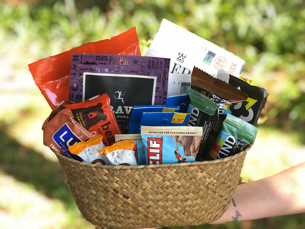 A basket of Cliff Bars, Kind Bars, Luna Bars, and other products for a giveaway.