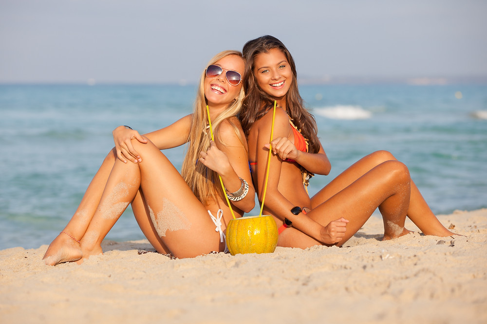Two girls sitting on the beach drinking out of a coconut.