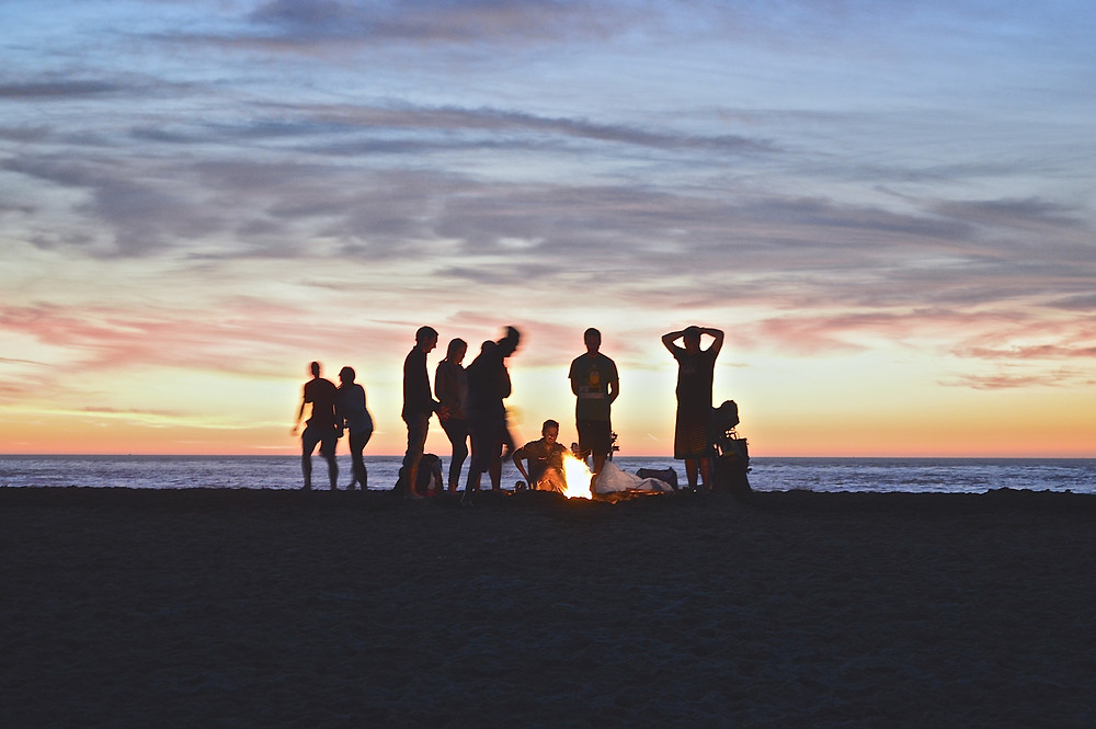 The sun setting with people gathered around a campfire on the beach.