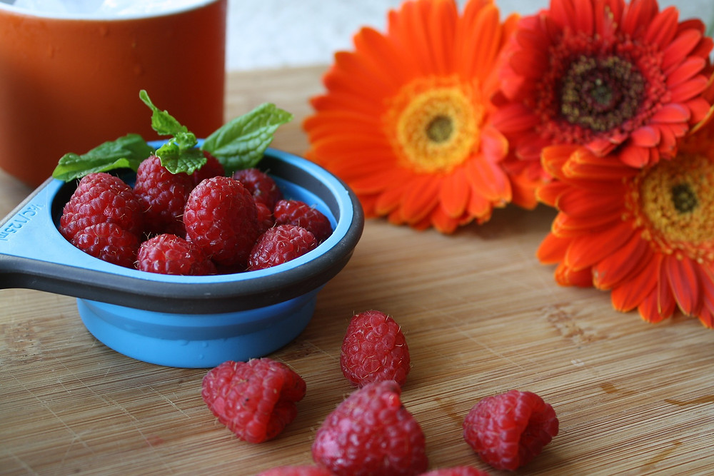 A small bowl of raspberries with orange flowers in the background.