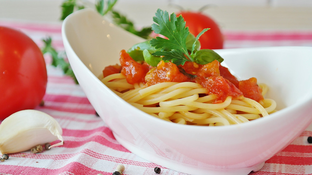 Spaghetti noodles with tomato sliced and garnish.