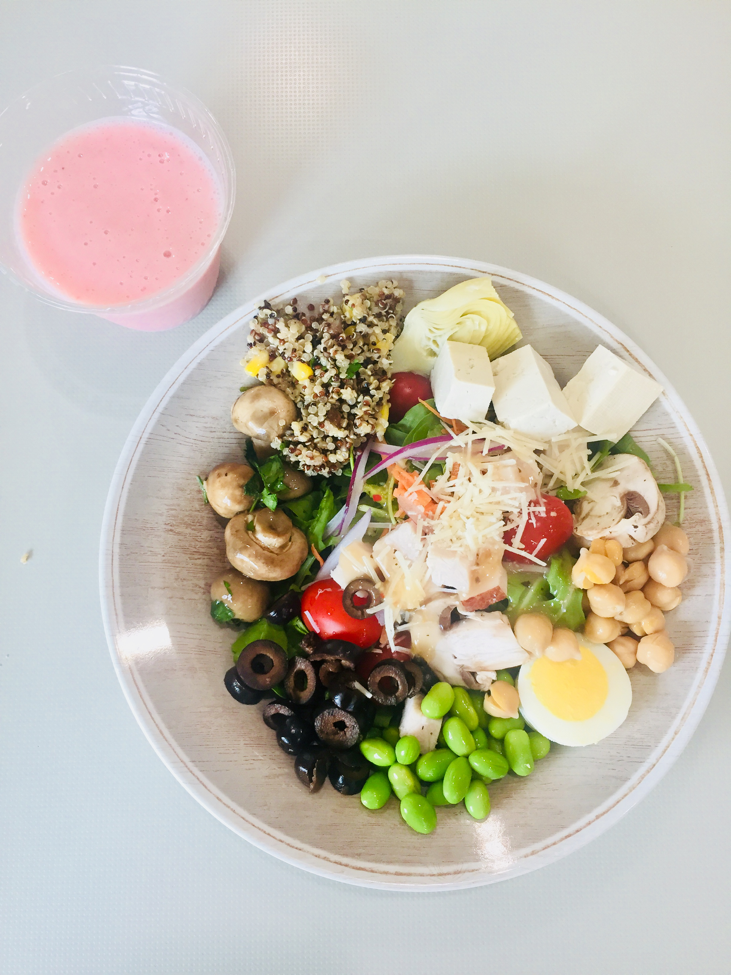 Bird's eye view of salad made in the cafe with mushrooms, olives, edamame, eggs, beans, and tofu with a side of a small smoothie.