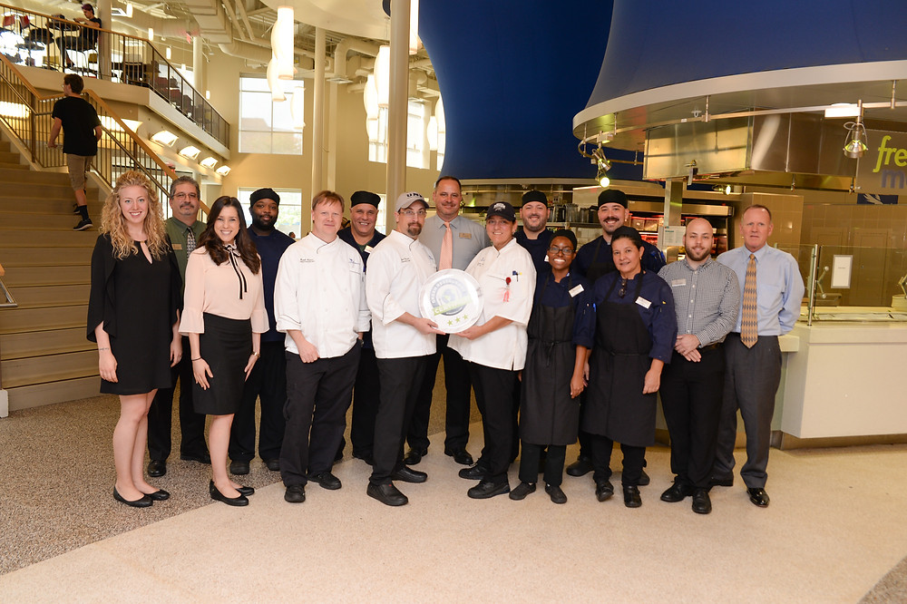 All the Chefs, managers, and directors involved with UNF Dining in the cafe holding the Green Restaurant certified plate.