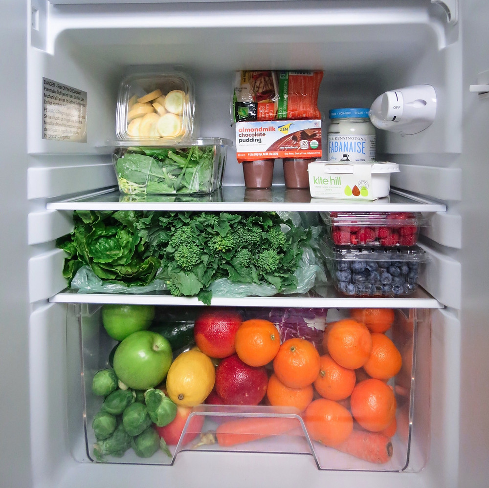 An inside of a fridge filled with chocolate pudding, tofu, and a large abundance of fresh fruits and vegetables.