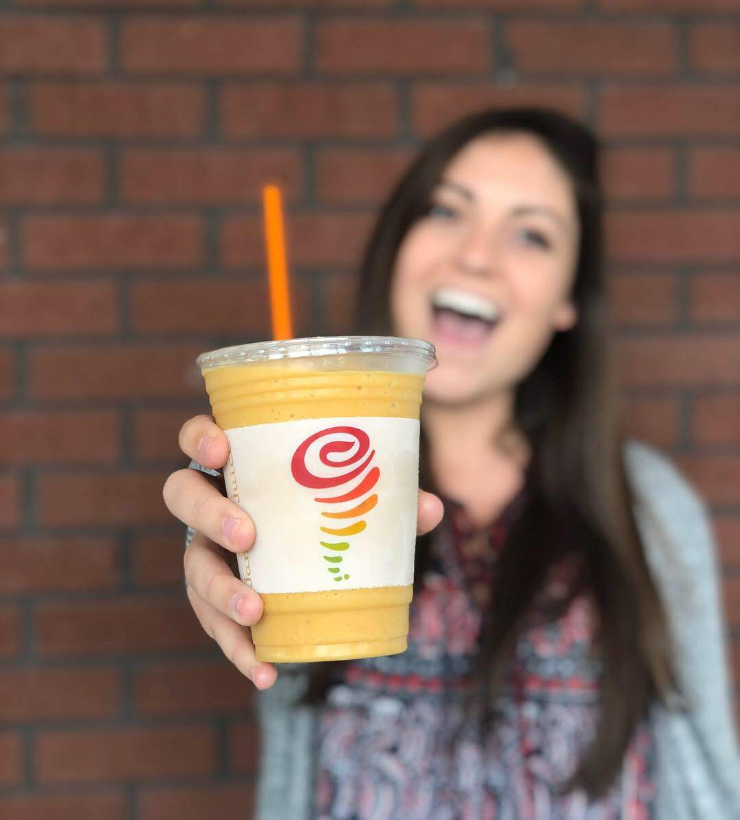 A female smiling with a Jahma Juice smoothie
