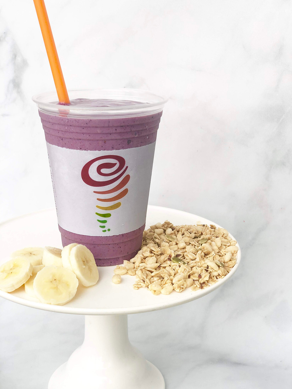 A jamba smoothie plated with oatmeal and banana slices.