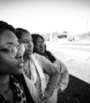 3 Black women standing by a railroad.