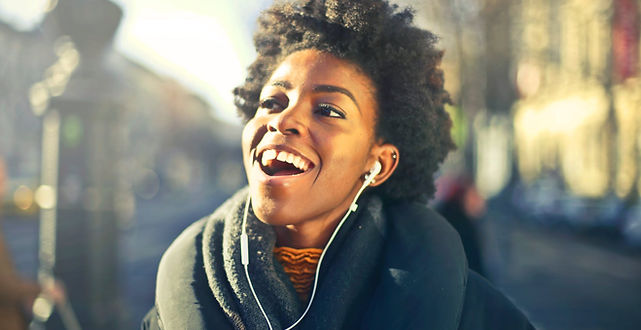 Young black woman with afro listening to music with white earbuds.