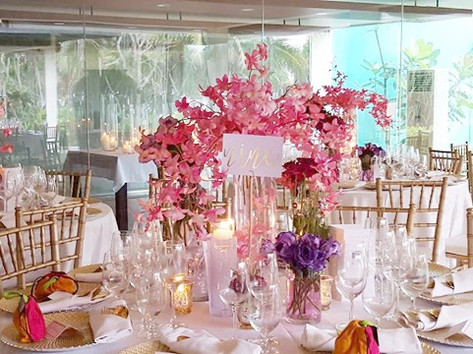 Opulent Orchid, Roses and Chrysanthemun centerpieces in a room surrounded by candles