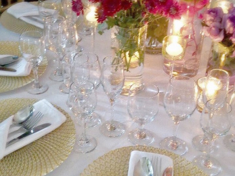 Gold charger plates  at wedding table setting twinkling in the candelight of the centerpiece.