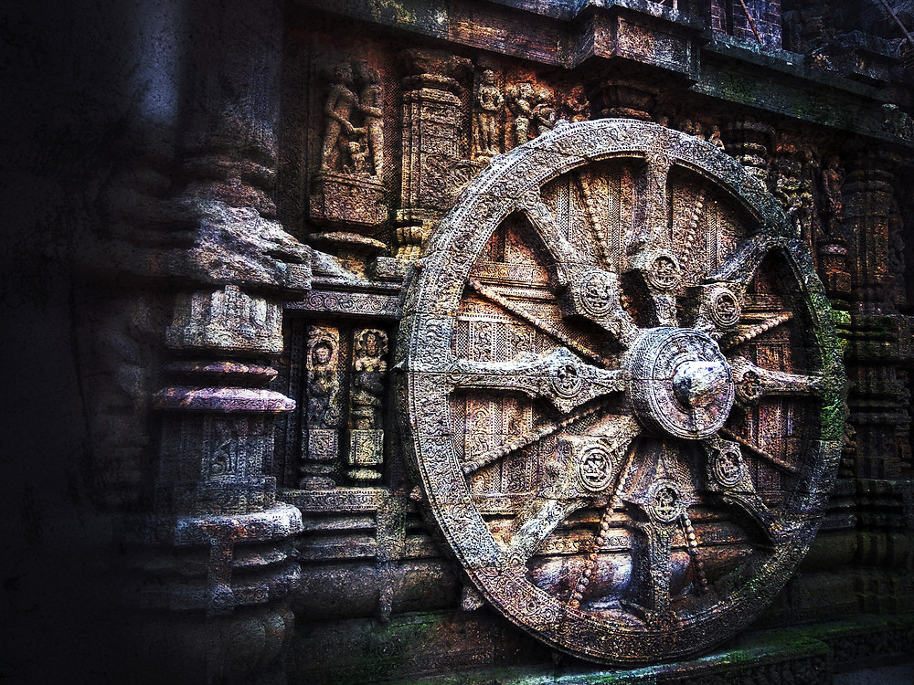 A wheel in a historical site mounted on a wall covered with ancient engravings.