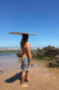 Chico con tabla de surf y bermuda plasti