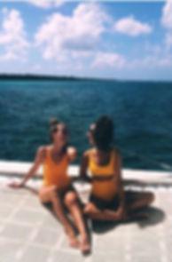 dos chicas sentadas en catamarán mirando