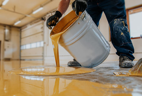 Worker applying a yellow epoxy resin buc
