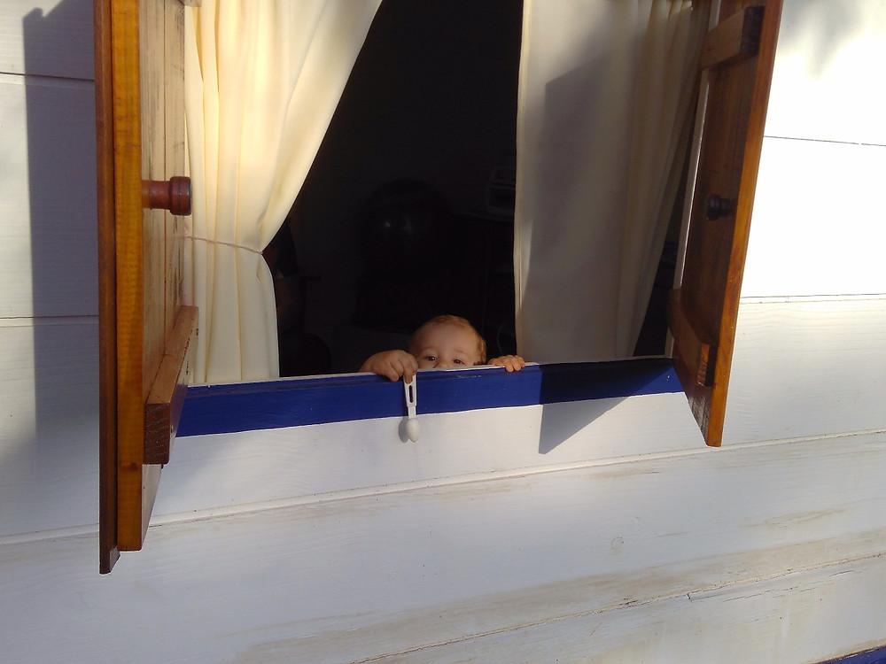 Criança na janela - brincar faz bem