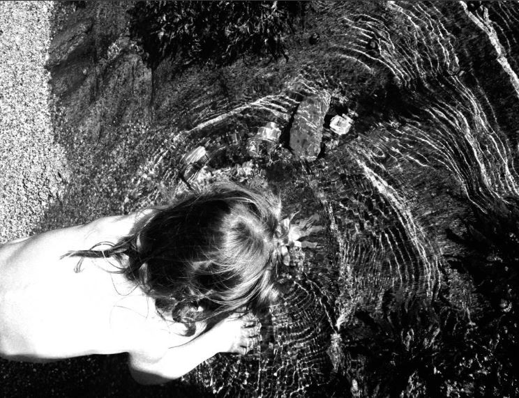 Petite fille mettant la main sous l'eau.