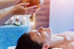 Woman enjoying a Ayurveda oil massage tr