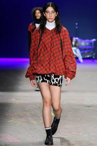 Model desfilando com casaco xadrez vermelho
