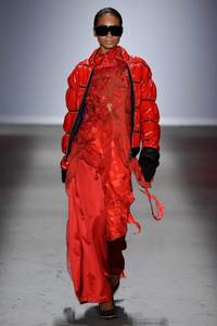 Modelo desfilando com conjunto vermelho