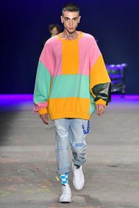 Modelo desfilando com calça jeans e casaco colorido