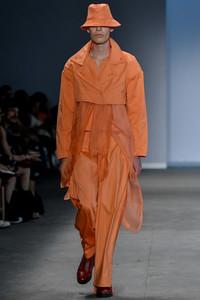 Modelo desfilando com conjunto laranja