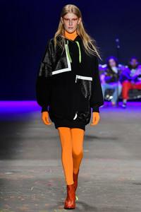 Modelo desfilando com calça laranja e casaco preto