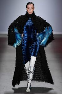 Modelo desfilando com macacao preto e azul
