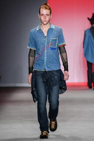 Modelo desfilando com camisa e calça jeans