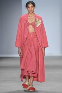 Modelo desfilando com conjunto rosa
