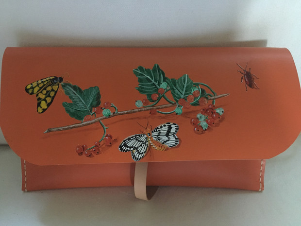 Leather clutch hand painted with a branch of berries and various insects