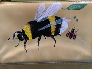 Patent leather clutch painted with a bee, an insect and peas