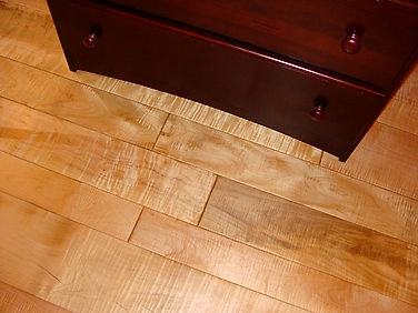 Beautiful Curly Hard Maple flooring shown in random widths, hand beveled edges and an oil/wax finish by Mahogany stained dresser
