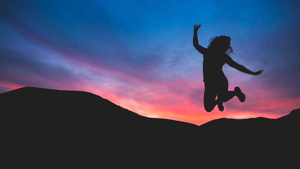 Joyful Woman Jumping Against SunsetPhoto by Austin Schmid on Unsplash