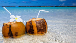 Two coconut cocktails on white sand beach next to clean sea water. Vacation and travel concept_edite